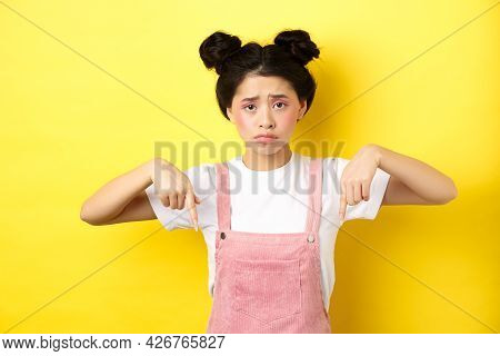 Sad Frowning Asian Girl Pointing Fingers Down At Unfair Thing, Looking Upset And Gloomy, Standing Wi