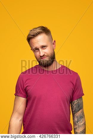 Bearded Man In Red T Shirt Raising Eyebrows And Looking At Camera With Sceptic Glance Against Yellow