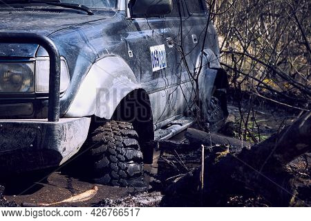 The 4x4 Suv Is Stuck In The Mud. The Wheels Of The Suv Are In Dirty Water. The Concept Of Adventure