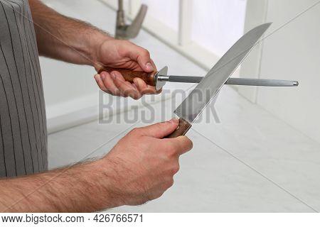 Man Sharpening Knife In Kitchen, Closeup View