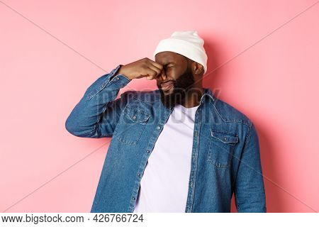 Disgusted African-american Man Shut Nose From Aversion, Displeased By Awful Bad Smell, Standing In B