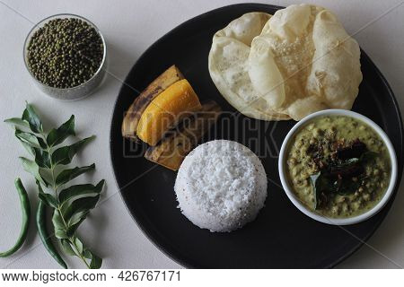 Steamed Rice Cake Served With Steamed Plantain, Green Gram Curry And Papad. A Favorite Dish Of Keral