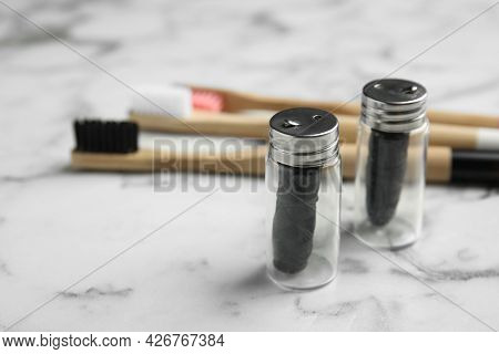 Biodegradable Dental Flosses In Glass Jars On White Marble Table. Space For Text