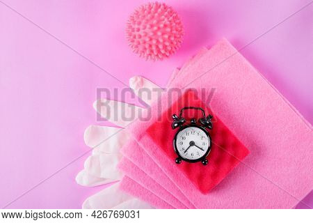Pink Cleaning Set. Alarm Clock, Rag, Foam Rubber Sponge, Laundry Ball And Latex Gloves On Pink Backg