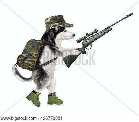 A Dog Husky In Military Uniform Is Walking With A Rifle With Optical Sight. White Background. Isolat