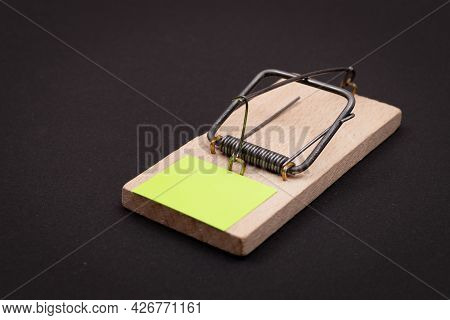 Blank Yellow Sheet Of Paper In Wooden Mousetrap - Template. Small Memo Paper In Mouse Trap On Black