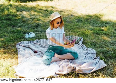 Charming Young Woman In Sunglasses And A Hat Taking A Selfie On A Smartphone During A Summer Picnic
