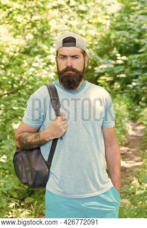 Standing Alone In Forest Outdoor With Sunset Nature On Background. Bearded Man With Backpack. Fashio