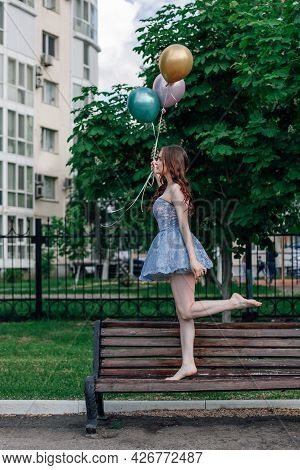 A Ballerina In A Corset Dress Walks On Tiptoe On A Bench In The Park Holding Balloons In Her Hands