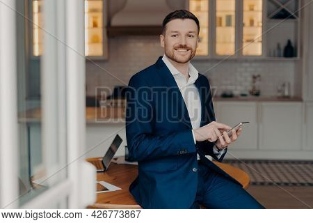 Horizontal Shot Of Man Employee Uses Great Business App Reads Good News Message Holds Mobile Phone P