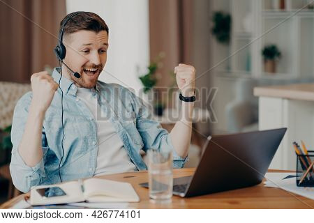 Overjoyed Triumphing Adult Man Clenches Fists Celebrates Success Looks Attentively At Laptop Screen