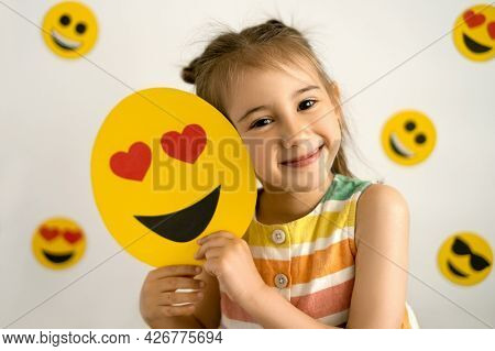 A Girl, Smiling With All Her Teeth, Holds A Love Emoji In Her Hands. World Emoji Day. Anthropomorphi