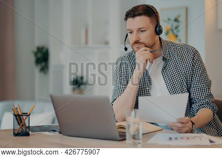 Serious Man Freelancer In Casual Wear Holding Document In Hand And Looking At Laptop Screen, Analyzi