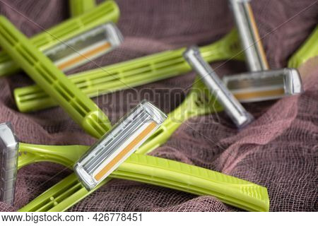 Personal Green Razors On A Red Background. Lots Of Sharp New Razors