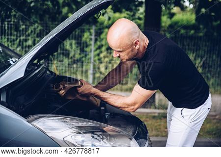 Bald Man Pouring Oil Into A Car In Front Of The House.