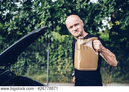 Handsome Man In Black T-shirt Holding Bottle With Engine Oil.