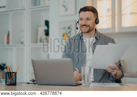 Smiling Bearded Guy Sitting At His Workplace And Holding Documents During Online Meeting, Male Freel