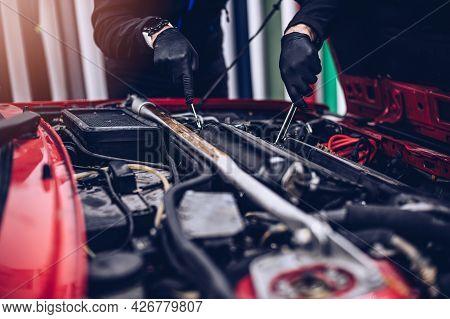 Car Mechanic Repairing Customer Engine With Wrench.