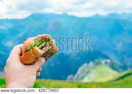 Man Eating Delicious Sandwich On Mountain On Trail