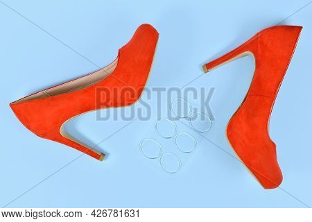 Shoe Insole Protection Gel Stickers For Relieving Pressure Points Next To Red High Heels On Blue Bac