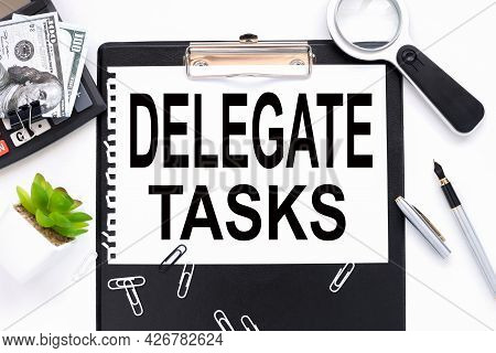 Delegate Tasks. Text On A White Sheet Of Paper Near A Magnifying Glass M Flowerpot In A Pot