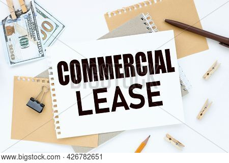 Commercial Lease. Text On White Notepad Paper. On A White Photo With Torn Paper