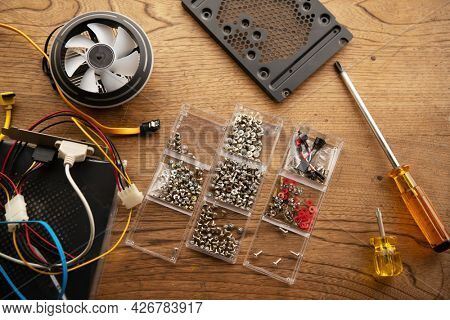 Assembling PCs. PC assembling screws and parts on a wooden table.