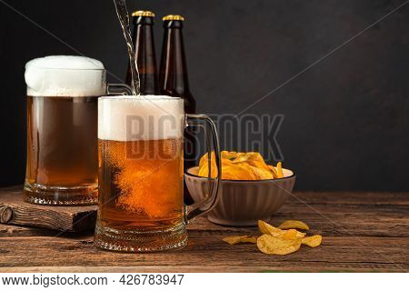 Filling Beer Mugs With Beer On The Background Of Chips And Bottles. Oktoberfest. Side View, Space Fo