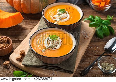 Two Servings Of Pumpkin Cream Soup With Cream On A Wooden Background. Side View. Autumn, Vegetarian