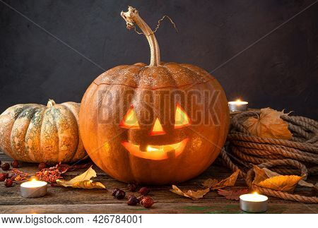 Pumpkin Lantern, A Halloween Symbol On A Dark Background With Foliage And Candles. Side View.