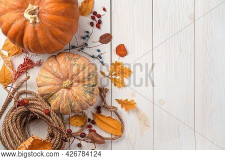 Background With Autumn Holiday Decor. Pumpkins And Autumn Foliage On A Wooden White Background. The