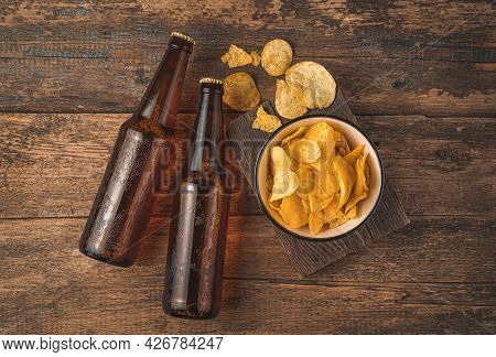 Dark Beer Bottles And Chips In A Bowl On A Wooden Background. Top View. Oktoberfest.