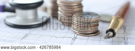 Cardiogram Stethoscope And Coins Lie On Table