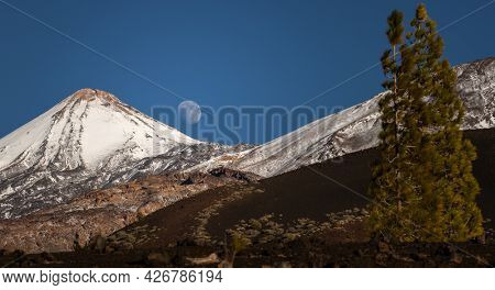 Colorful scenic landscape of moon rise in Tenerife national park of Teide. El Teide with moon rising by its side.