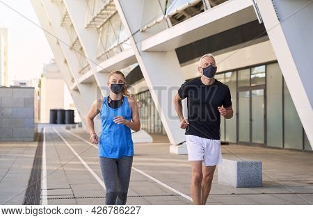 Active Mature Couple Wearing Protective Face Masks Jogging Together In Urban Environment