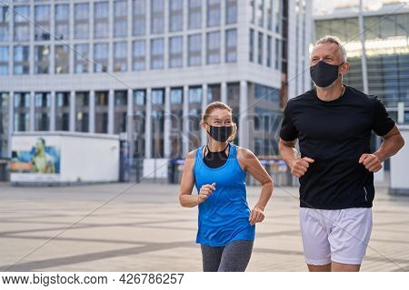 Motivated Middle Aged Couple, Woman And Man Wearing Protective Masks Jogging Outdoors In The City To