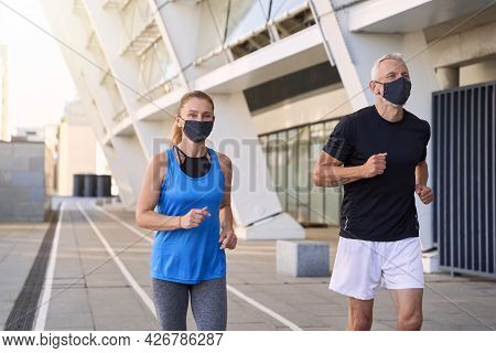 Sportive Mature Couple Wearing Protective Face Masks Jogging Together In Urban Environment