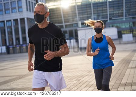 Sporty Middle Aged Couple Wearing Protective Masks Running In Urban Environment, Staying Active Duri