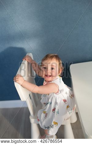 Cute Baby Girl Wearing Dress Sitting On The White Chair In The Room And Looking At The Camera. Verti