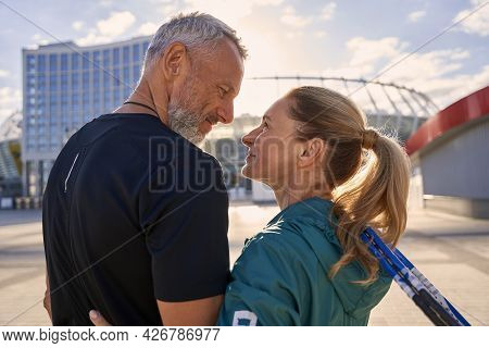 Lovely Sportive Middle Aged Couple Smiling At Each Other While Standing Together Outdoors, Ready For