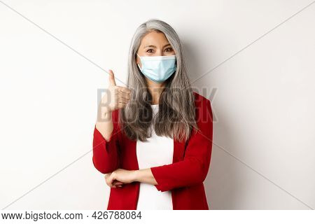 Coronavirus And Business Concept. Asian Female Entrepreneur In Face Mask Looking Cheerful, Showing T