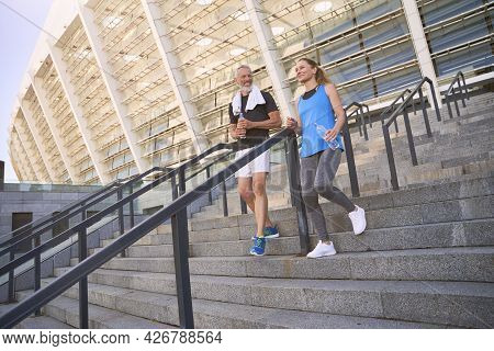 Attractive Sportive Middle Aged Couple, Man And Woman In Sportswear Training Together Outdoors