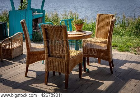 A Wooden Table And Four Wicker Chairs - Garden Furniture Standing On A Bright Wooden Patio, On The R