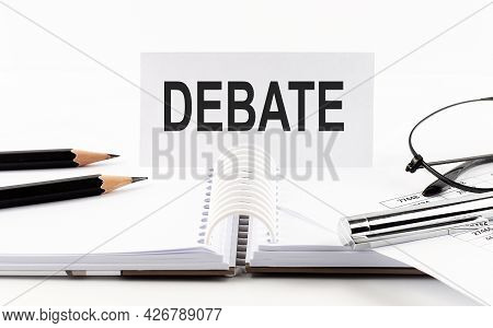 Text Debate On Paper Card,pen, Pencils, Glasses,financial Documentation On The Table - Business Conc