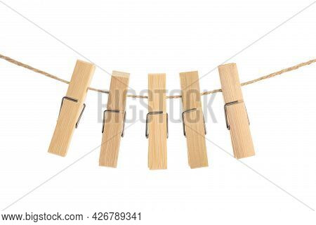 Many Wooden Clothespins On Rope Against White Background