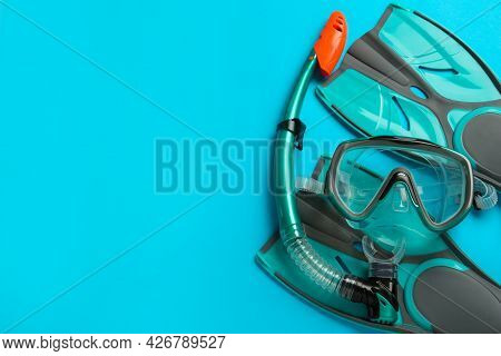 Pair Of Turquoise Flippers And Mask On Light Blue Background, Flat Lay. Space For Text