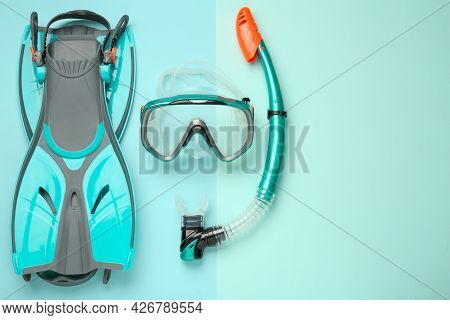 Pair Of Flippers, Snorkel And Diving Mask On Turquoise Background, Flat Lay