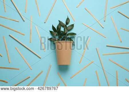 Paper Cup With Green Twigs Surrounded By Bamboo Straws And Sticks On Turquoise Background, Flat Lay.