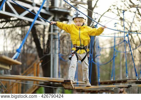 Little Boy Having Fun In Adventure Park For Children Amoung Ropes, Stairs, Bridges. Outdoor Climbing