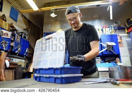 Metalwork Craftsman Making Handmade Lamp At Workshop. Man Worker Choose A Screws From The Box During